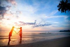 Jeunes couples jugeant des mains en forme de coeur sur la plage de mer Images stock