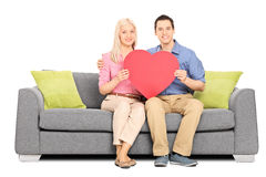 Jeunes couples jugeant le grand coeur rouge posé sur le sofa Image stock