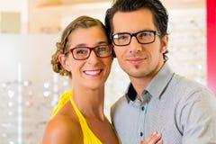 Jeunes couples à l'opticien avec des glaces Photo stock