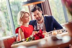 Jeunes couples la date dans des acclamations potables se reposantes de vin de restaurant regardant la caméra curieuse images libres de droits