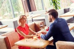 Jeunes couples la date dans le restaurant se reposant jugeant des mains regardant l'un l'autre heureuses photo stock
