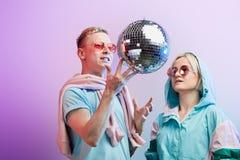 Jeunes couples ? la mode des danseurs posant avec la boule de disco sur le fond violet photo libre de droits