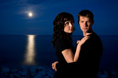 Jeunes couples la nuit par la mer Image stock