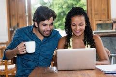 Jeunes couples latino-américains d'amour à l'intérieur à l'ordinateur Image libre de droits