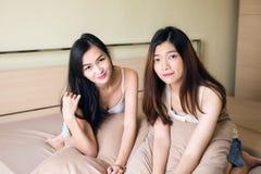 Jeunes couples lesbiens asiatiques de femmes sur le lit Photos libres de droits