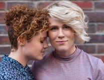 Jeunes couples lesbiens satisfaits se tenant affectueusement ensemble dehors Photographie stock libre de droits