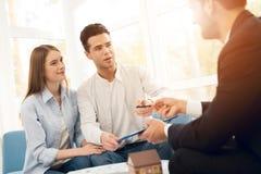 Jeunes couples lors d'une réunion avec un agent immobilier Le type et la fille font un contrat avec la propriété de achat d'agent Photographie stock