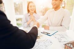 Jeunes couples lors d'une réunion avec un agent immobilier Le type et la fille font un contrat avec la propriété de achat d'agent Images stock