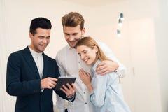 Jeunes couples lors d'une réunion avec un agent immobilier Le type et la fille font un contrat avec la propriété de achat d'agent Photographie stock libre de droits