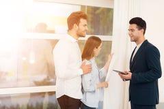Jeunes couples lors d'une réunion avec un agent immobilier Le type et la fille font un contrat avec la propriété de achat d'agent Photo stock