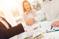 Jeunes couples lors d'une réunion avec un agent immobilier Le type et la fille font un contrat avec la propriété de achat d'agent Photo libre de droits
