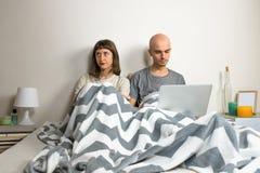 Jeunes couples malheureux ou mécontents dans le lit Image stock