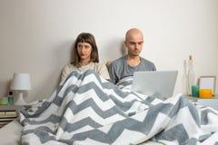 Jeunes couples malheureux ou mécontents dans le lit Images libres de droits