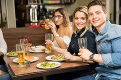 Jeunes couples mangeant avec des amis Images stock
