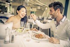Jeunes couples mangeant dans un restaurant Photos stock