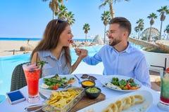 Jeunes couples mangeant dans un restaurant de piscine Photos stock