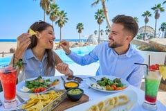 Jeunes couples mangeant dans un restaurant de piscine Photographie stock libre de droits