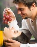 Jeunes couples mangeant des raisins photo stock