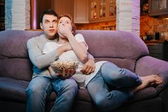 Jeunes couples mangeant du maïs éclaté et observant un film à la maison sur le divan, effrayé photos libres de droits