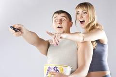Jeunes couples mangeant du maïs éclaté, TV de observation Photographie stock libre de droits