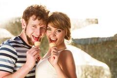 Jeunes couples mangeant la crème glacée extérieure Image stock