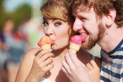Jeunes couples mangeant la crème glacée extérieure Photographie stock