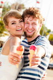 Jeunes couples mangeant la crème glacée extérieure Photos stock