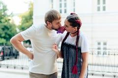 Jeunes couples mangeant une grande sucrerie sur le fond d'une construction en plein air Photo libre de droits