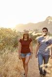 Jeunes couples marchant à la lumière du soleil lumineuse Photo stock