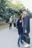 Jeunes couples marchant avec des amis Le type étreint la fille Images libres de droits