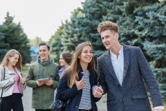 Jeunes couples marchant avec des amis Le type tient la main du ` s de fille Photo stock