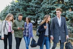 Jeunes couples marchant avec des amis Le type tient la main du ` s de fille Image libre de droits