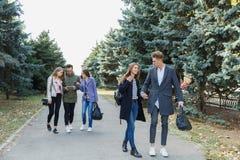 Jeunes couples marchant avec des amis Le type tient la main du ` s de fille Images libres de droits