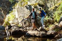 Jeunes couples marchant avec le chien de chiens de traîneau en canyon près de l'eau Photos stock
