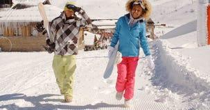 Jeunes couples marchant dans la neige lourde d'hiver Photo stock