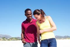 Jeunes couples marchant ensemble sur la plage Photo stock