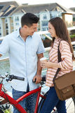 Jeunes couples marchant et faisant un cycle pour travailler dans l'environnement urbain Photo stock