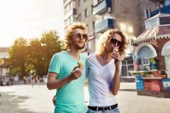 Jeunes couples marchant et léchant la crème glacée  Photos libres de droits