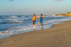 Jeunes couples marchant nu-pieds sur une plage humide à Image libre de droits