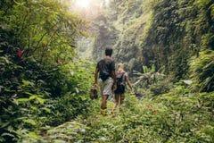 Jeunes couples marchant par des bois Images stock