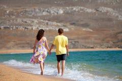 Jeunes couples marchant sur la plage Image stock