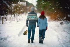 Jeunes couples marchant sur la route neigeuse Photo stock