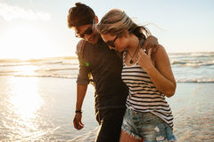 Jeunes couples marchant sur le bord de la mer Photos stock