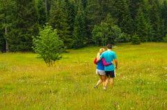 Jeunes couples marchant sur le pré Images libres de droits