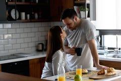 Jeunes couples mariés beaux prenant le petit déjeuner pendant le matin à la maison dans leurs pyjamas photo libre de droits