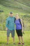 Jeunes couples mignons augmentant ensemble sur un beau flanc de coteau de montagne Photos stock