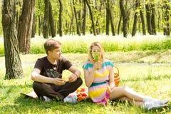 Jeunes couples mignons ayant la nourriture sur le pique-nique Photo libre de droits