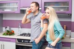 Jeunes couples mignons buvant du jus d'agrumes frais Photo stock