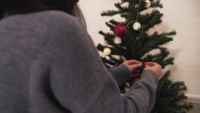 Jeunes couples mignons décorant l'arbre de Noël dans la chambre avant des vacances Concept de temps de nouvelle ann?e et de No?l  banque de vidéos