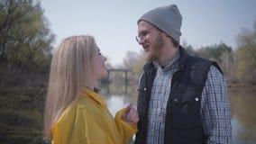 Jeunes couples mignons de portrait marchant en nature en dehors de la ville pr?s de la rivi?re Belle fille blonde dans un imperm? banque de vidéos